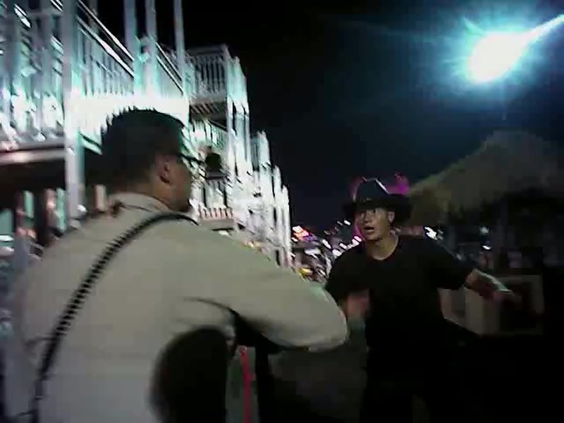 FILE - In this Sunday, Oct. 1, 2017, file image taken from police body cam video released Wednesday, July 25, 2018, by the Las Vegas Metropolitan Police Department, a law enforcement official, left, directs concertgoers to safety, as authorities search for what they thought were multiple shooters inside and outside a Las Vegas Strip hotel, where a gunman firing from upper-floor windows killed 58 people and injured hundreds. (Las Vegas Metropolitan Police Department via AP, File)