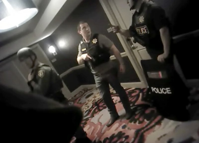 FILE - In this Oct. 1, 2017, file image from police body cam video released by the Las Vegas Metropolitan Police Department on July 25, 2018, shows law enforcement officers in a hallway at the Mandalay Bay Resort and Casino while searching for a shooter in Las Vegas. (Las Vegas Metropolitan Police Department via AP, File)