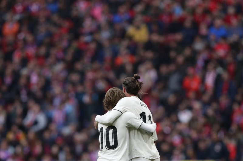 Real Madrid's Gareth Bale, right, celebrates with Real Madrid's Luka Modric after scoring his side's 3rd goal during a Spanish La Liga soccer match between Atletico Madrid and Real Madrid at the Metropolitano stadium in Madrid, Spain, Saturday, Feb. (AP Photo/Manu Fernandez)