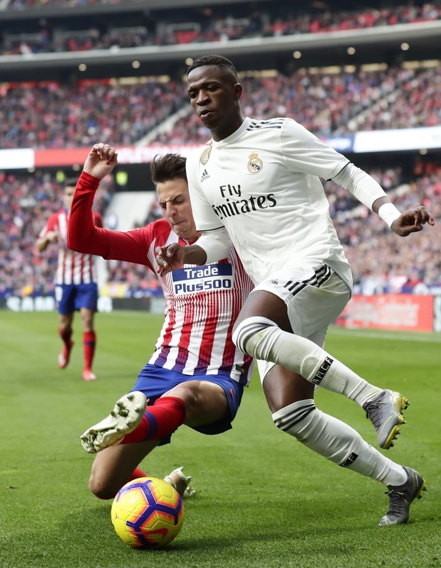 Real Madrid's Vinicius Junior, right, is tackled by Atletico Madrid's Santiago Arias during a Spanish La Liga soccer match between Atletico Madrid and Real Madrid at the Metropolitano stadium in Madrid, Spain, Saturday, Feb. (AP Photo/Manu Fernandez)