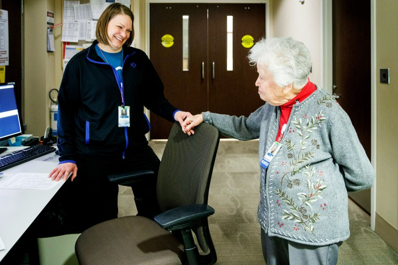 In this Monday, Jan. 28, 2019 photo, radiological technician Tracia Haun, left, visits with Jean Bailey, 98, as she volunteers at Methodist Women's Hospital in Omaha, Neb. (Ryan Soderlin /Omaha World-Herald via AP)