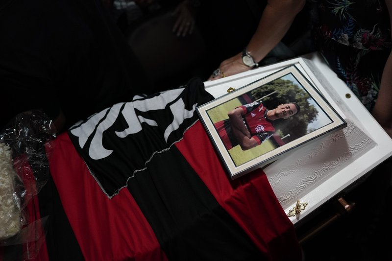 A photo of the young soccer Arthur Vinicius, one of the victims of a fire at a Brazilian soccer academy, is displayed over his coffin during his funeral in Volta Redonda, Brazil, Saturday, Feb. (AP Photo/Leo Correa)