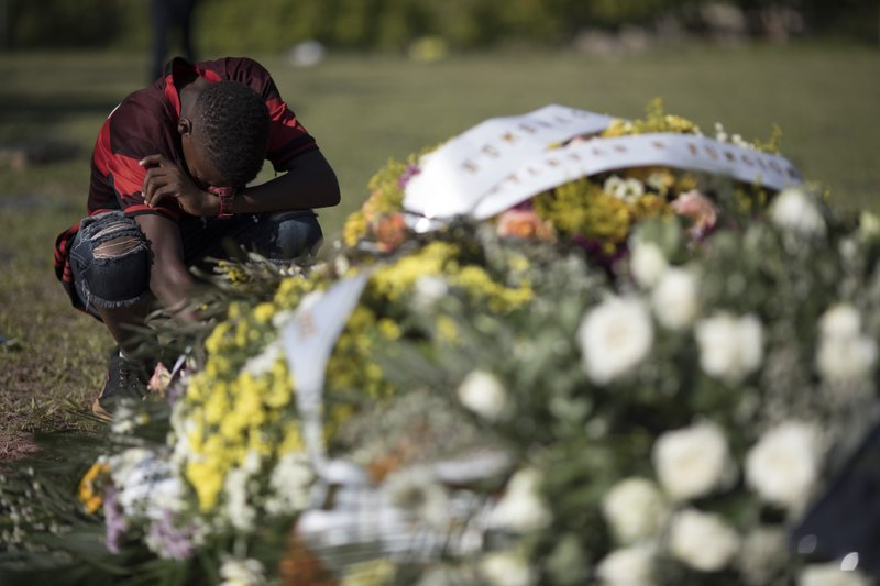 A friend, wearing a Flamengo soccer kit, grieves at the grave of the young soccer player Arthur Vinicius, one of the victims of a fire at a Brazilian soccer academy, after his burial in Volta Redonda, Brazil, Saturday, Feb. (AP Photo/Leo Correa)