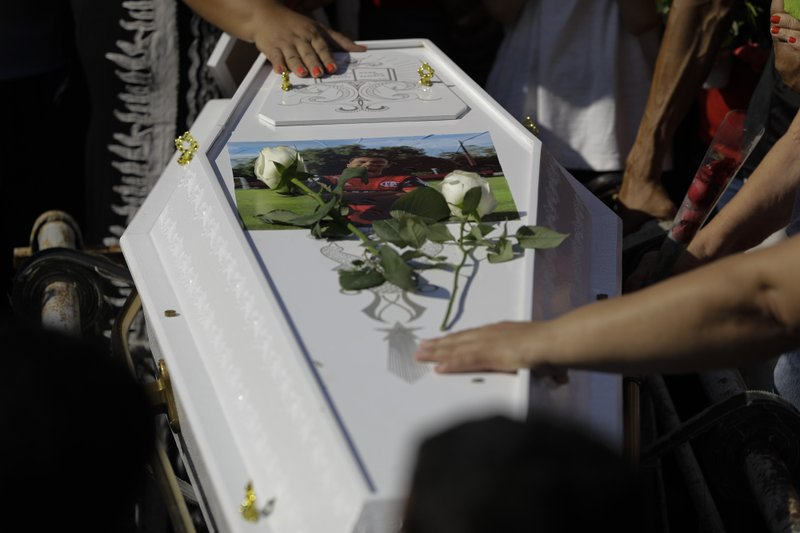 Friends and relatives grieve during the burial of the young soccer player Arthur Vinicius, one of the victims of a fire at a Brazilian soccer academy, in Volta Redonda, Brazil, Saturday, Feb. (AP Photo/Leo Correa)