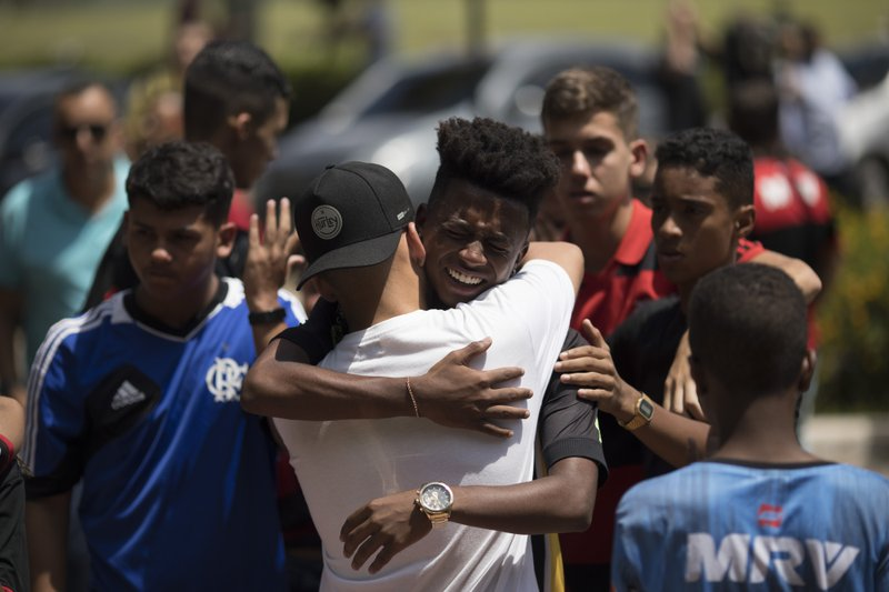Friends grieve during the funeral of the young soccer player Arthur Vinicius, one of the victims of a fire at a Brazilian soccer academy, in Volta Redonda, Brazil, Saturday, Feb. (AP Photo/Leo Correa)