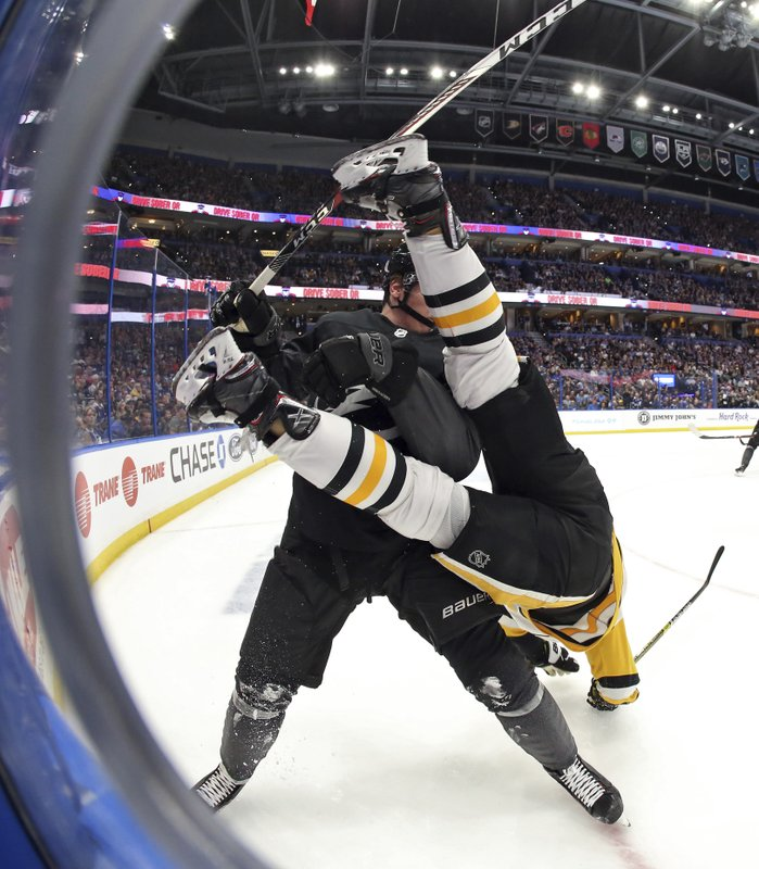 Tampa Bay Lightning defenseman Mikhail Sergachev, left, upends Pittsburgh Penguins left wing Tanner Pearson during the third period of an NHL hockey game Saturday, Feb. (AP Photo/Chris O'Meara)