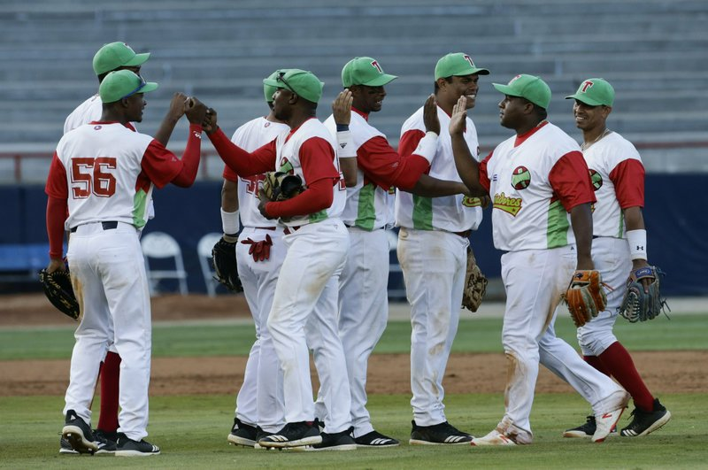 Players of Cuba's Los Leneros de las Tunas celebrate at the end of the ninth inning after defeating Venezuela's Cardenales de Lara on their Caribbean Series baseball tournament game at Rod Carew stadium in Panama City, Saturday, Feb. (AP Photo/Arnulfo Franco)