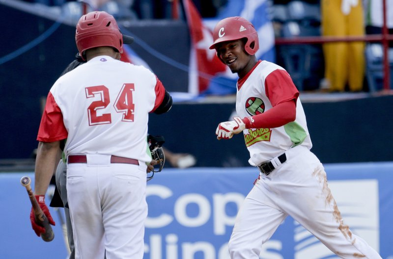 Yuniesky Larduet, right, of Cuba's Los Leneros de las Tunas, celebrates with teammate Frederich Cepeda after scoring a run against Venezuela's Cardenales de Lara, during the sixth inning of their Caribbean Series baseball tournament game at Rod Carew stadium in Panama City, Saturday, Feb. (AP Photo/Arnulfo Franco)