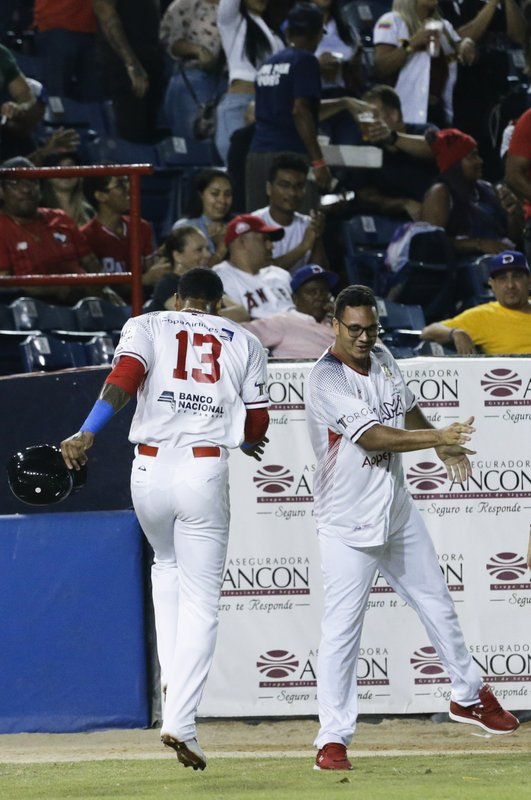 Allen Cordoba, left, of Panama's Los Toros de Herrera, is congratulated by a teammate after scoring a run against Puerto Rico's Cangrejeros de Santurce during the fourth inning in the Caribbean Series baseball tournament at Rod Carew stadium in Panama City, Saturday, Feb. (AP Photo/Arnulfo Franco)