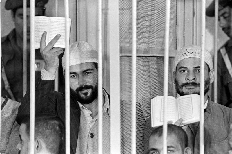 FILE - In this Nov. 30, 1981 file photograph, Khalid al-Islambouli, left, and Abdel Hamid Abdel Aal hold up open Qurans during the second day of their trial in Cairo, Egypt, Monday, Nov. (AP Photo, File)