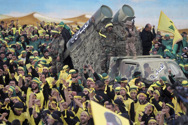 FILE - In this Oct. 27, 2015 file photograph, Hezbollah fighters stand atop a truck mounted with mock rockets as supporters chant slogans during a rally to mark the 13th day of the Shiite mourning period of Muharram, in Nabatiyeh, Lebanon. (AP Photo/Mohammed Zaatari, File)