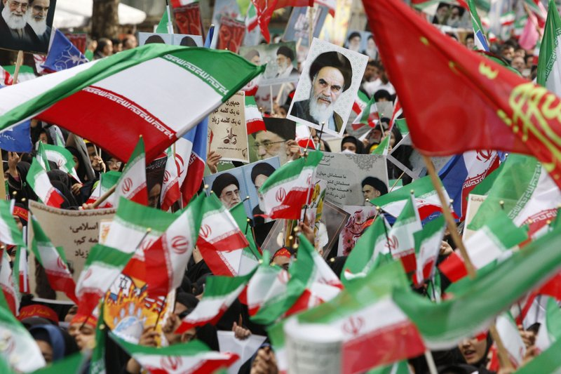 FILE - In this Nov. 4, 2009 file photograph, waving flags, Iranian school girls attend an annual demonstration in front of the former U. (AP Photo/Vahid Salemi, File)