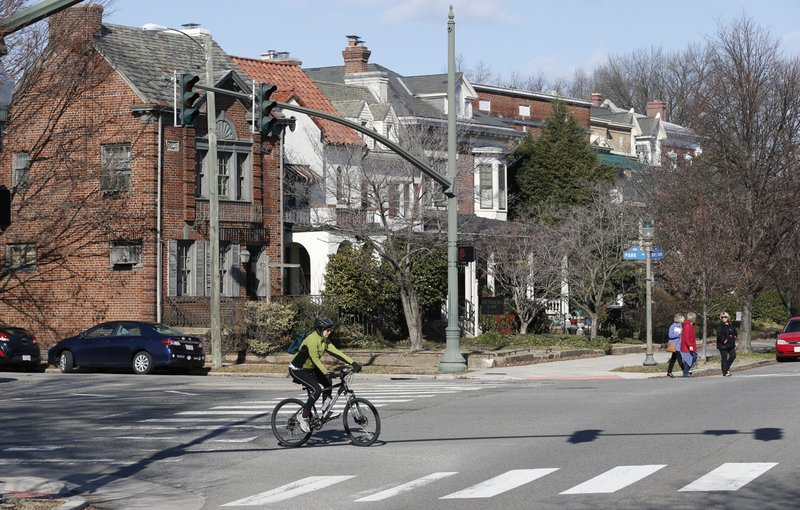 In this Jan. 25, 2019, photo cyclists and pedestrians cross The Boulevard in Richmond, Va. A city councilwoman and others are attempting to get the Boulevard named after tennis star Arthur Ashe. (AP Photo/Steve Helber)