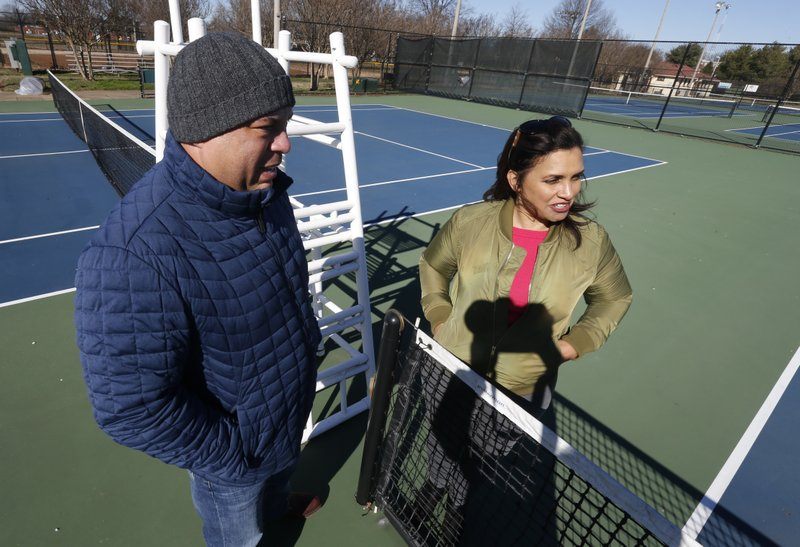 In this Jan. 10, 2019, photo David Harris Jr., left, the nephew of Arthur Ashe, and Richmond City Council member, Kim Gray, right, look over the tennis courts on the Boulevard which were tennis star Arthur Ashe was banned from in Richmond, Va. (AP Photo/Steve Helber)