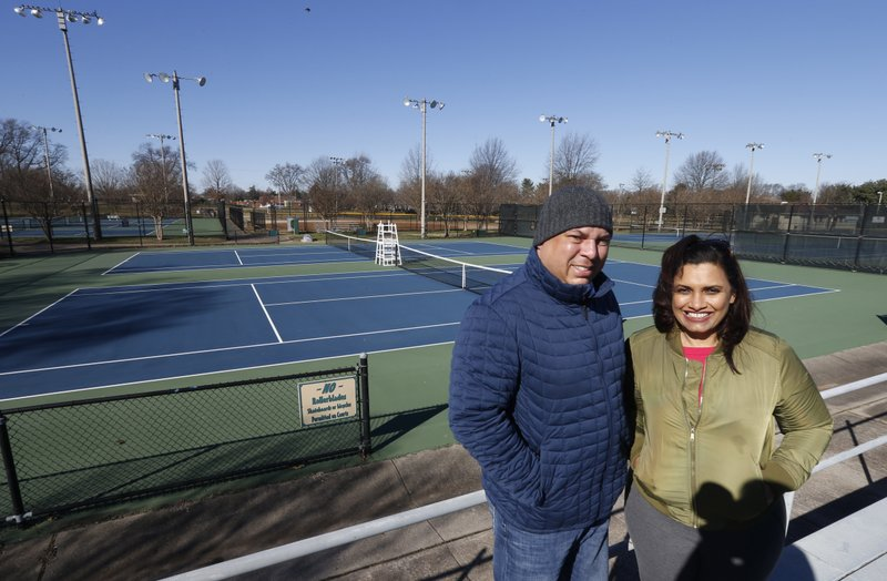 In this Jan. 10, 2019, photo David Harris Jr., left, the nephew of Arthur Ashe, and Richmond City Council member, Kim Gray, right, pose at the tennis courts on the Boulevard which were tennis star Arthur Ashe was banned from in Richmond, Va. (AP Photo/Steve Helber)