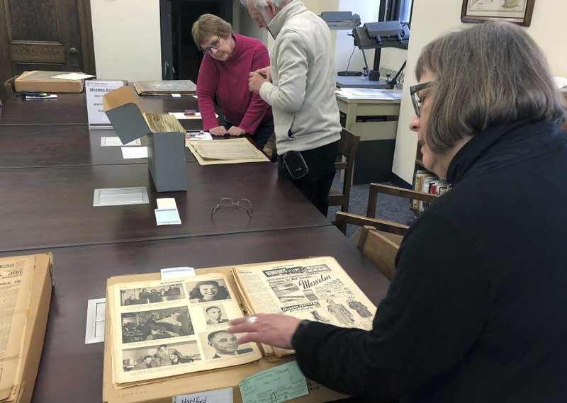 In this Nov. 29, 2018 photo, Christine Gauvreau, project coordinator for the Connecticut Digital Newspaper Project, pages through old issues of the Hartford Chronicle, a World War II era black-owned and operated newspaper, at the Connecticut State Library in Hartford, Conn. (AP Photo/Susan Haigh)