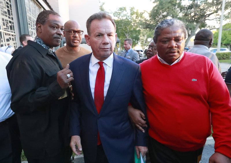 FILE- In this Jan. 11, 2019, file photo, suspended Broward County Sheriff Scott Israel, center, leaves a news conference surrounded by supporters in Fort Lauderdale, Fla. (AP Photo/Wilfredo Lee, File)