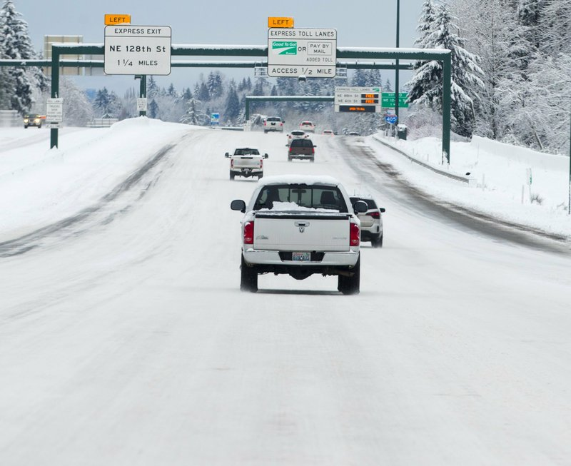 Cars drive on snow and ice on Interstate 405 approaching Kirkland, Wash., on Saturday, Feb. 9, 2019. This view looks south from Northeast 160th Street. (Mike Siegel/The Seattle Times via AP)
