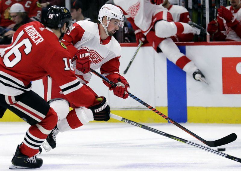 Detroit Red Wings center Dylan Larkin, front right, controls the puck against Chicago Blackhawks center Marcus Kruger, left, during the first period of an NHL hockey game Sunday, Feb. (AP Photo/Nam Y. Huh)