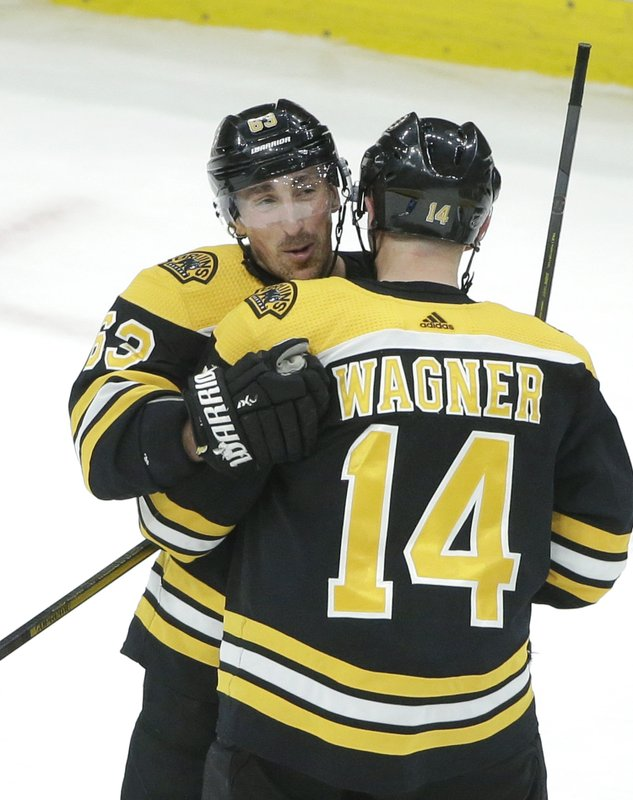 Boston Bruins' Brad Marchand, left, celebrates with teammate Chris Wagner (14) after scoring the winning goal in overtime against the Colorado Avalanche in an NHL hockey game, Sunday, Feb. (AP Photo/Steven Senne)