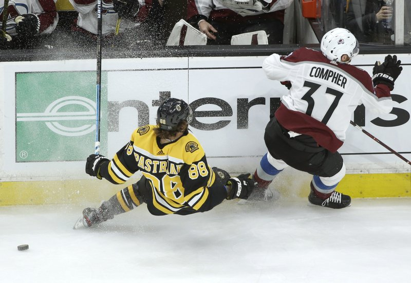 Boston Bruins's David Pastrnak, of Czech Republic, (88) and Colorado Avalanche's J.T. Compher (37) skate past the puck during the first period of an NHL hockey game, Sunday, Feb. (AP Photo/Steven Senne)