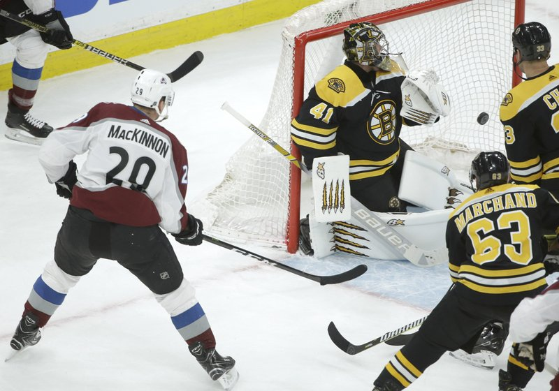 Colorado Avalanche's Nathan MacKinnon (29), left, shoots the puck into the net past Boston Bruins' Jaroslav Halak, of Slovakia (41) to score as Bruins' Brad Marchand (63) and Zdeno Chara, of Slovakia, top right, look on during the first period of an NHL hockey game, Sunday, Feb. (AP Photo/Steven Senne)