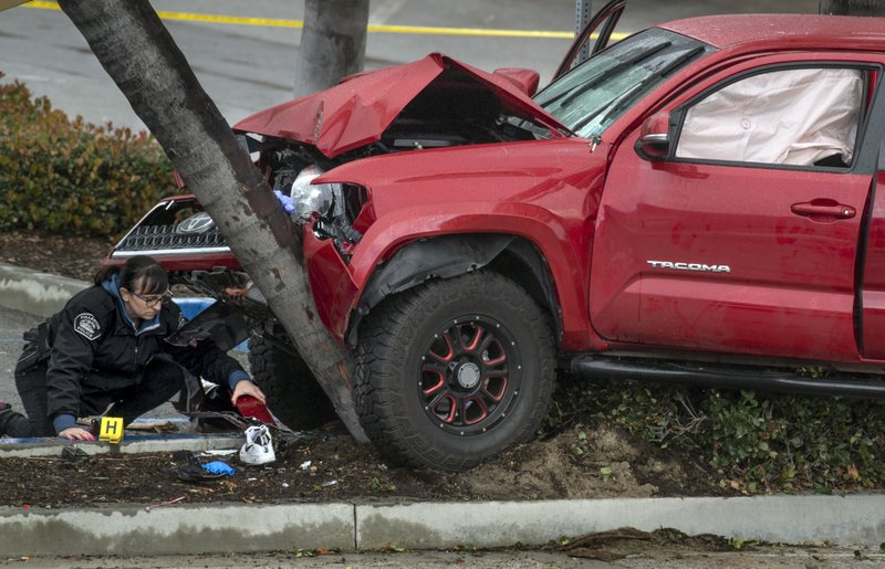 Heather Barclay, bottom left, an accident investigator with the Fullerton Police Department, gathers evidence from an early-morning accident involving a suspected DUI driver on Sunday, Feb. (Mindy Schauer/The Orange County Register via AP)