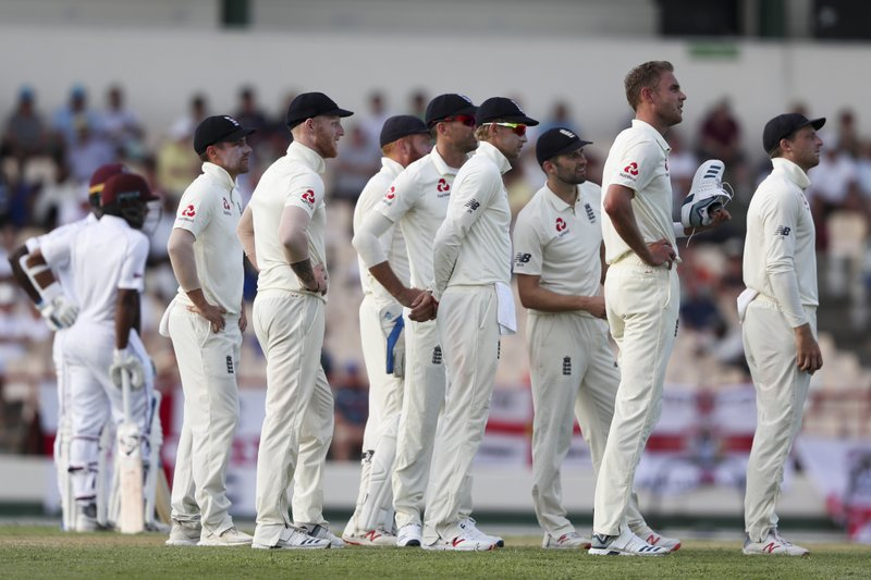 England's Stuart Broad holds his shoes as he waits with teammates for a review during day two of the third cricket Test match against West Indies at the Daren Sammy Cricket Ground in Gros Islet, St. (AP Photo/Ricardo Mazalan)