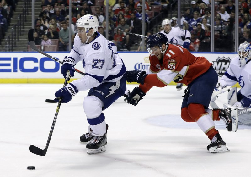 Tampa Bay Lightning defenseman Ryan McDonagh (27) skates with the puck as Florida Panthers left wing Jonathan Huberdeau (11) pursues during the second period of an NHL hockey game, Sunday, Feb. (AP Photo/Lynne Sladky)
