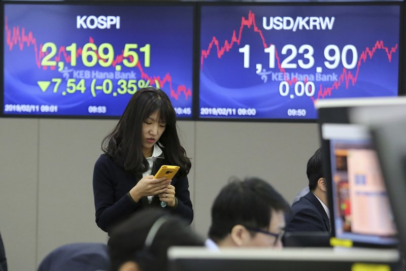 A currency trader watches her smartphone at the foreign exchange dealing room of the KEB Hana Bank headquarters in Seoul, South Korea, Monday, Feb. (AP Photo/Ahn Young-joon)