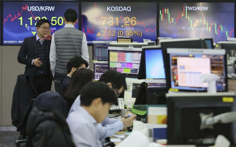 Currency traders work at the foreign exchange dealing room of the KEB Hana Bank headquarters in Seoul, South Korea, Monday, Feb. (AP Photo/Ahn Young-joon)