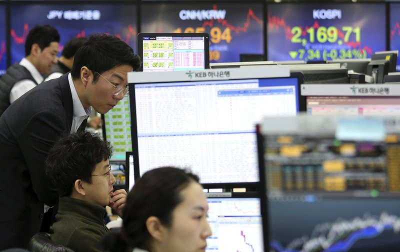 Currency traders watch monitors at the foreign exchange dealing room of the KEB Hana Bank headquarters in Seoul, South Korea, Monday, Feb. (AP Photo/Ahn Young-joon)