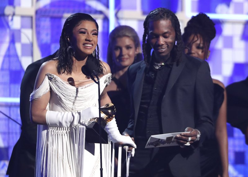 Cardi B, left, accepts the award for best rap album for