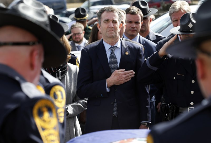 Virginia Gov. Ralph Northam, left, and his wife Pam, watch as the casket of fallen Virginia State Trooper Lucas B. (AP Photo/Steve Helber, Pool)