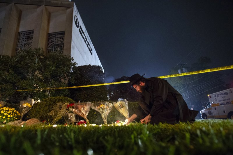 FILE - In this Oct. 27, 2018 photo, Rabbi Eli Wilansky lights a candle after a mass shooting at Tree of Life Synagogue in Pittsburgh's Squirrel Hill neighborhood. (Steph Chamber/Pittsburgh Post-Gazette via AP, File)