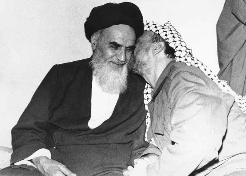 FILE - In this Feb. 18, 1979 file photo, Palestinian Liberation Organization leader Yasser Arafat, right, kisses Ayatollah Ruhollah Khomeini, during a meeting in Tehran, Iran. (AP Photo, File)