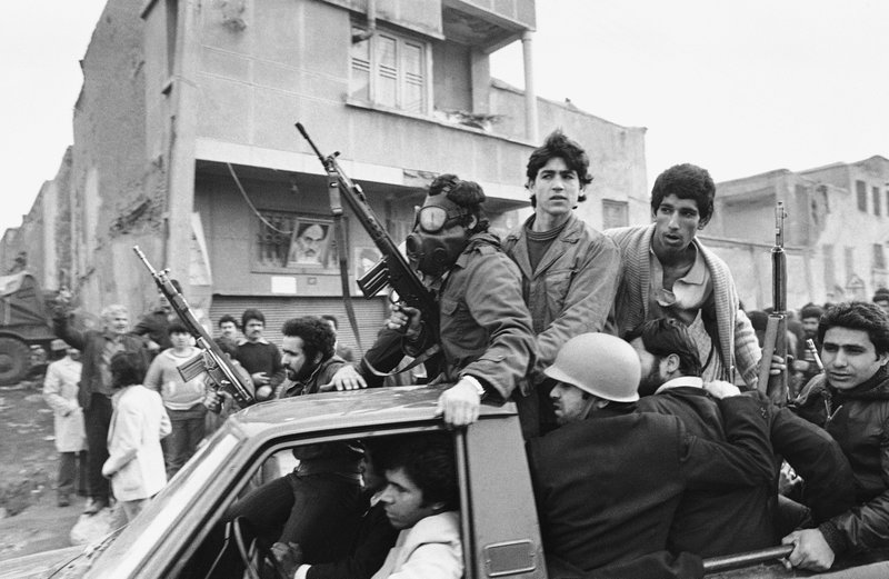 FILE - In this Feb. 12, 1979 file photo, armed rebels, one wearing a gas mask, ride in a truck near the headquarters of Ayatollah Khomeini, in Tehran, Iran. (AP Photo/Campion, File)