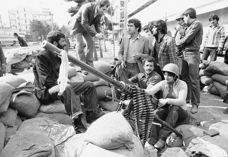 FILE - In this Feb. 13, 1979 file photo, an Iranian woman sits at a heavy weapon in Tehran Street, Tehran, Iran. (AP Photo/Michel Lipchitz, File)