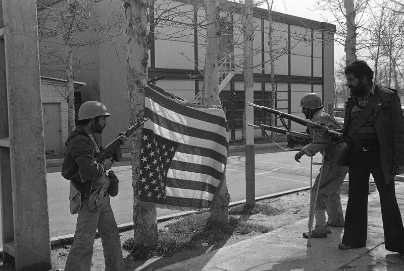 FILE - In this Feb. 12, 1979 file photo, Iranian rebels pose with a U.S. flag they bayonetted upside down on trees at Sultanabad Garrison northeast of Tehran, Iran. (AP Photo/Saris, File)