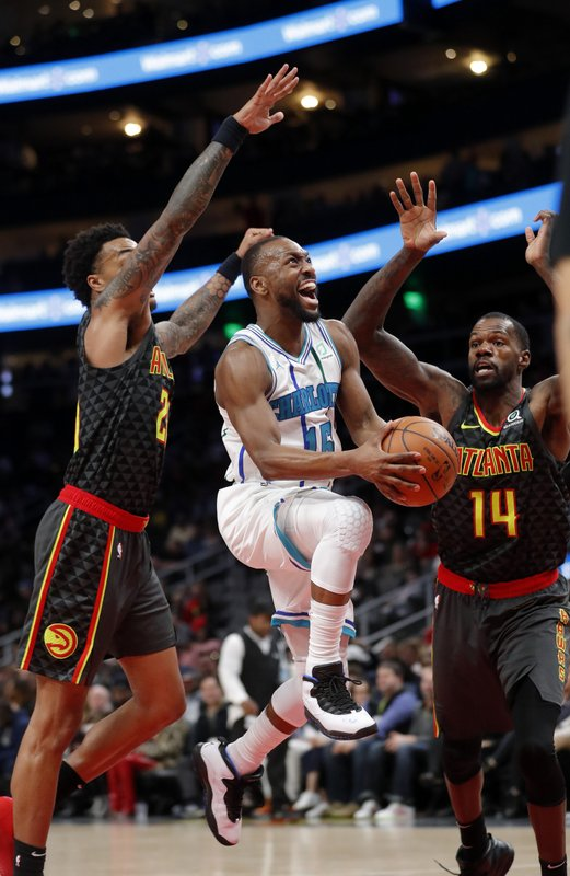 Charlotte Hornets guard Kemba Walker (15) goes between Atlanta Hawks' John Collins (20) and Dewayne Dedmon (14) during the second half of an NBA basketball Saturday, Feb. (AP Photo/John Bazemore)