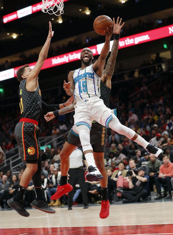 Charlotte Hornets guard Kemba Walker (15) scores as Atlanta Hawks guard Trae Young (11) defends during the second half of an NBA basketball Saturday, Feb. (AP Photo/John Bazemore)