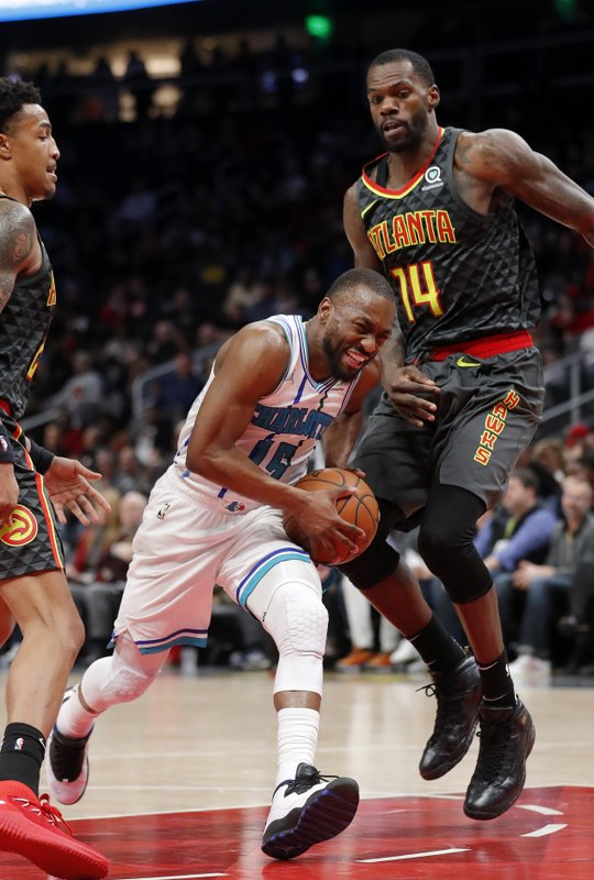 Charlotte Hornets guard Kemba Walker (15) drives against Atlanta Hawks center Dewayne Dedmon (14) during the second half of an NBA basketball Saturday, Feb. (AP Photo/John Bazemore)