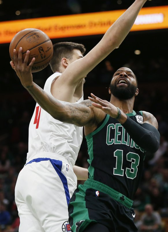 Boston Celtics' Marcus Morris (13) shoots against Los Angeles Clippers' Milos Teodosic (4) during the first half of an NBA basketball game in Boston, Saturday, Feb. (AP Photo/Michael Dwyer)