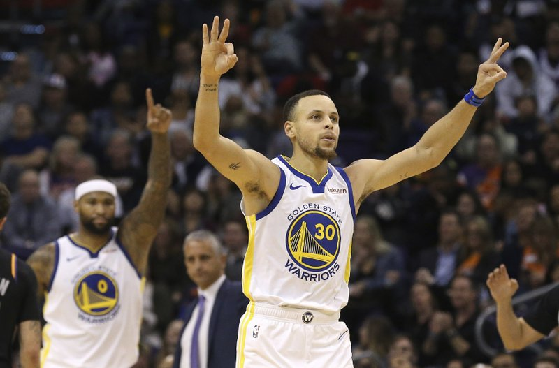 Golden State Warriors guard Stephen Curry (30) celebrates his 3-pointer against the Phoenix Suns along with Warriors center DeMarcus Cousins (0) during the second half of an NBA basketball game Friday, Feb. (AP Photo/Ross D. Franklin)