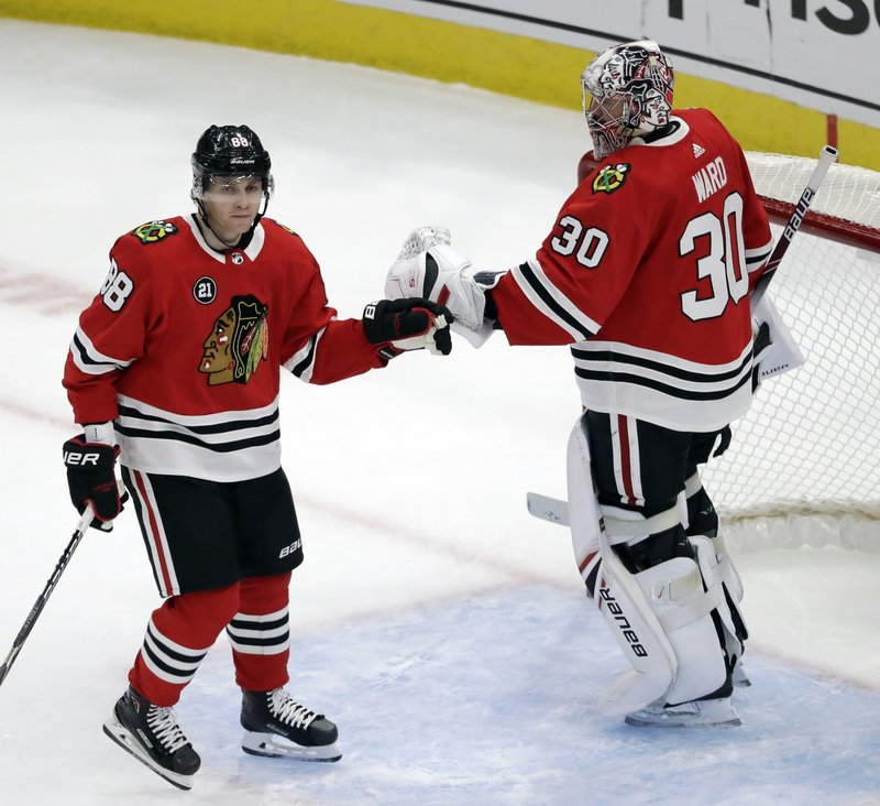 Chicago Blackhawks right wing Patrick Kane, left, celebrates with goalie Cam Ward after scoring a goal against the Detroit Red Wings during the third period of an NHL hockey game Sunday, Feb. (AP Photo/Nam Y. Huh)
