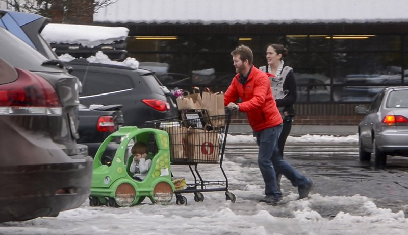 Jesse and Sarah Fees have their children along on a trip in North Tacoma, Wash., to restock their kitchen, Sunday, Feb. (Peter Haley/The News Tribune via AP)