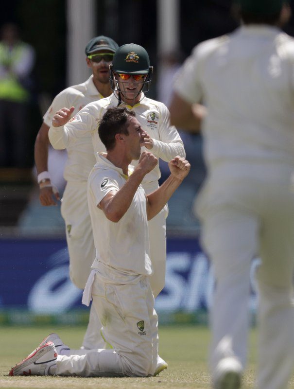 Australia's Pat Cummins, front left, celebrates his caught and bowled on Sri Lanka's Lahiru Thirimanne on day 4 of their cricket test match in Canberra, Monday, Feb. (AP Photo/Rick Rycroft)
