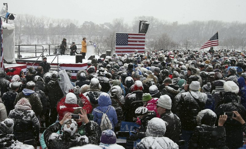 Democratic Sen. Amy Klobuchar, left, addresses a snowy rally where she announced she is entering the race for president Sunday, Feb. (AP Photo/Jim Mone)