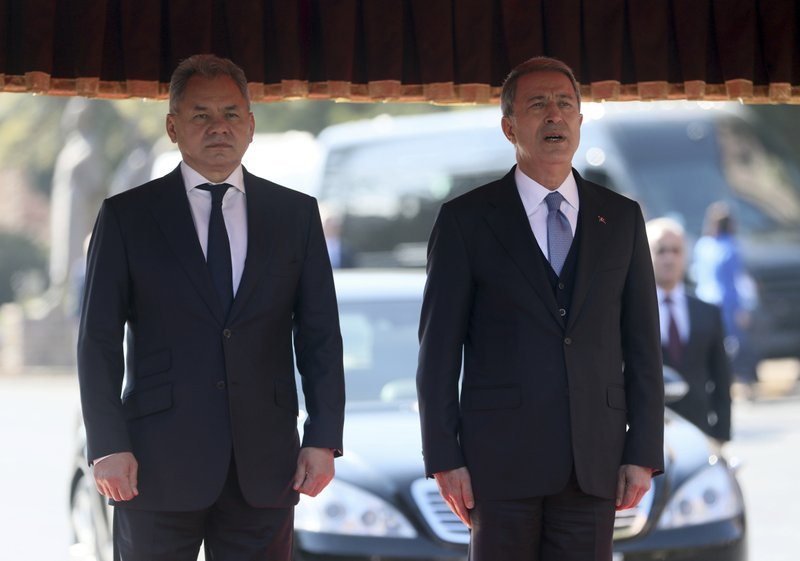Turkish Defence Minister Hulusi Akar, right, and Russia's Defence Minister Sergei Shoigu listen to national anthems during a ceremony in Ankara, Turkey, Monday, Feb. (Turkish Defence Ministry via AP, Pool)