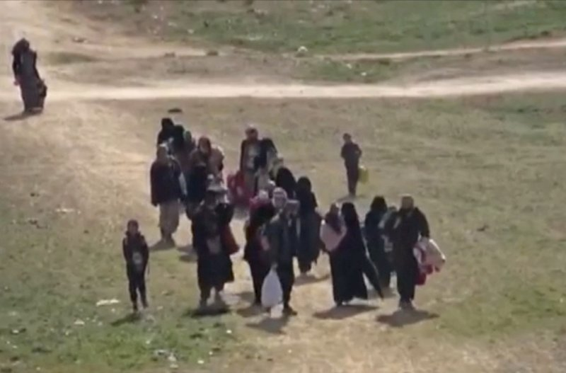 In this Sunday, Feb. 10, 2019 image from video provided by Hawar News Agency, ANHA, an online Kurdish news service, civilians flee fighting near Baghouz, Syria. (ANHA via AP)